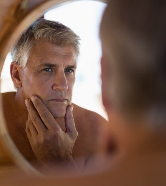 Man looking at mirror in cottage